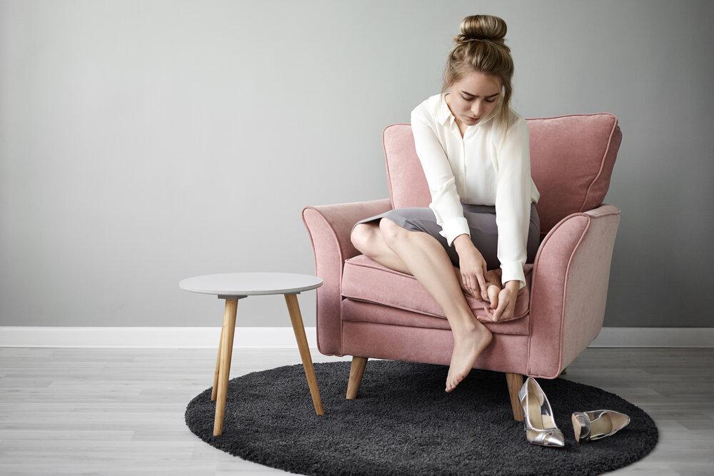 unavená mladá žena v spoločenskom oblečení, ktorá sedí v kresle a masíruje si chodidlo na zmiernenie bolesti, pretože má po celý deň topánky na vysokom podpätku.