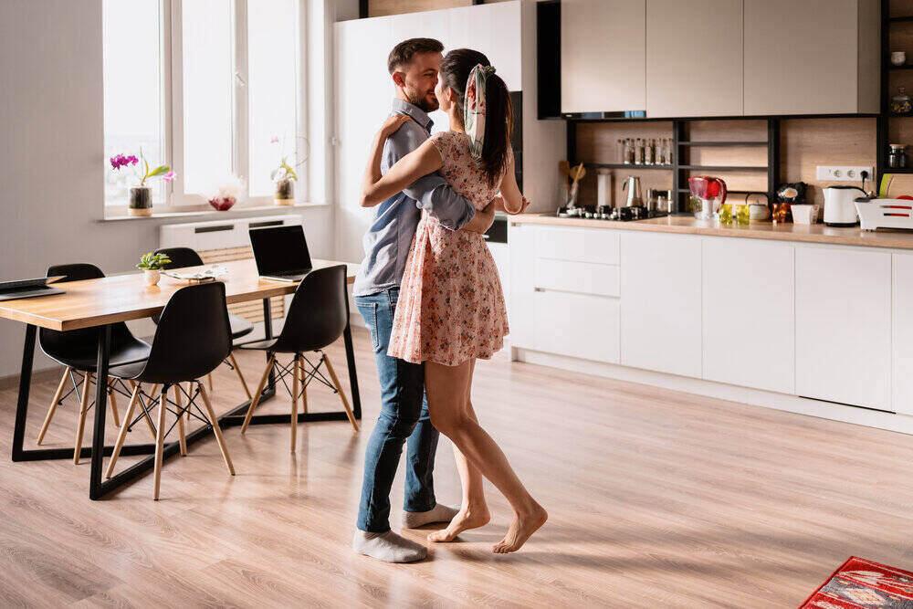 Šťastný mladý pár tancuje doma v modernom bývaní.