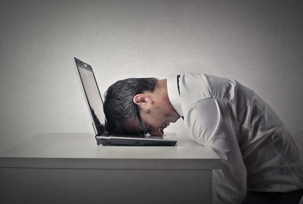Unevený muž sediaci za notebookom. Nedarí sa mu v práci.