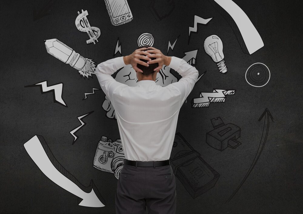 Zmätený muž si chytá hlavu pri pohľade na grafiku na čiernej stene