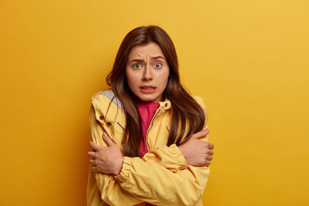 Nespokojná brunetka cíti stres a zimu, objíma sa, aby sa zahriala, má pršiplášť na prechádzky počas daždivého veterného počasia