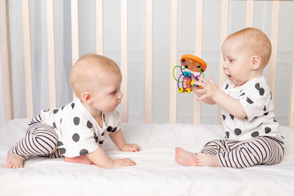 dve dvojčatá vo veku 8 mesiacov sa hrajú v postieľke