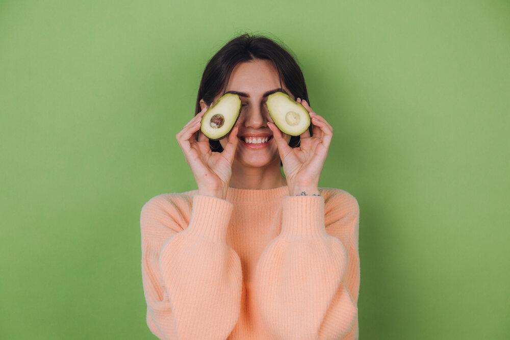 mladá žena v oranžovom svetríku na zelenom pozadí sa teší z avokáda