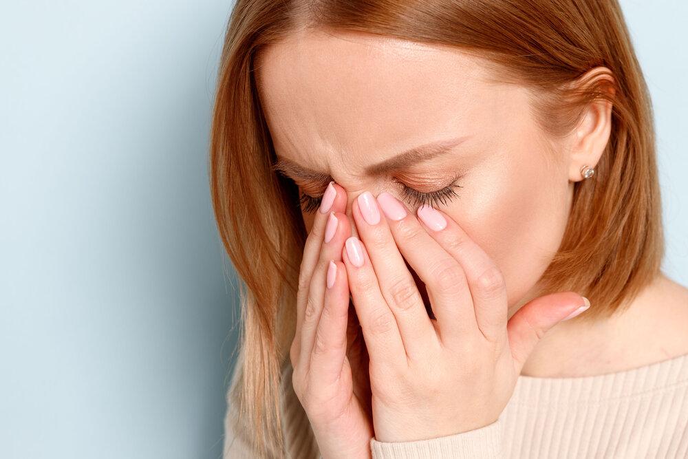 portrét mladej ženy, ktorá má problém s kontaktnými šošovkami, trením si opuchnutých očí v dôsledku peľu a alergiou na prach. Syndróm suchého oka