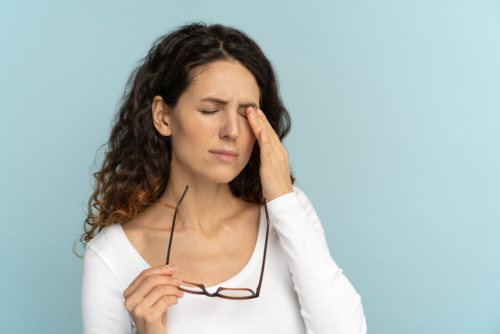 Ospalá mladá žena drží okuliare šúchajúce si oči, po práci na počítači sa cíti unavená. Má namáhané očí.
