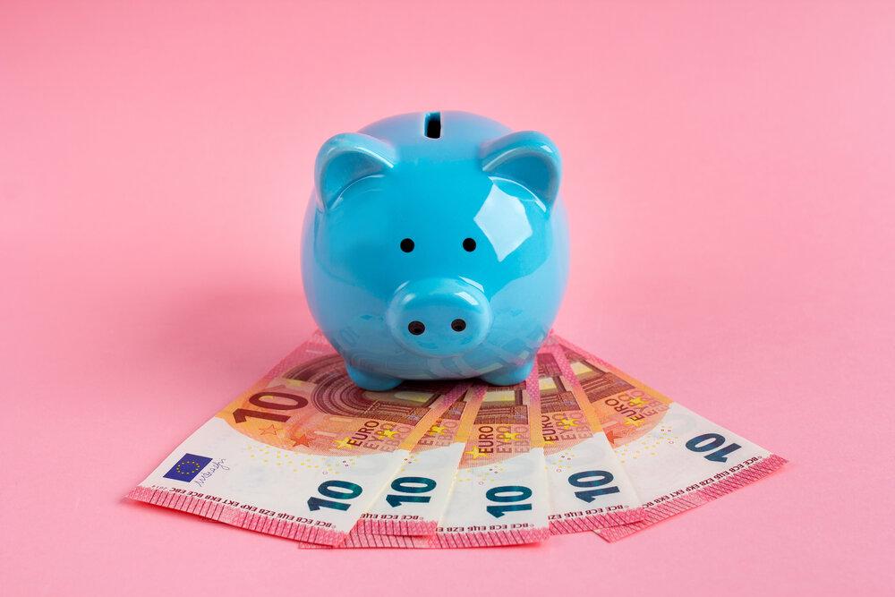 Modré prasiatko s eurobankovkami na ružovom pozadí. Koncept úspory financií.