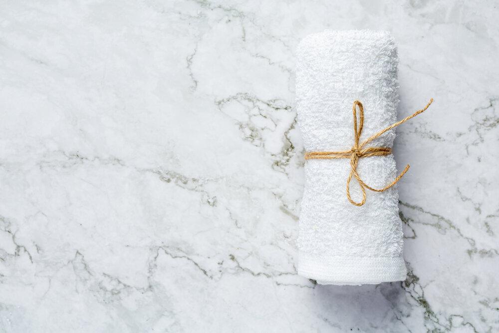 zrolovaný biely uterák na kúpeľné ošetrenie položený na podlahu z bieleho mramoru
