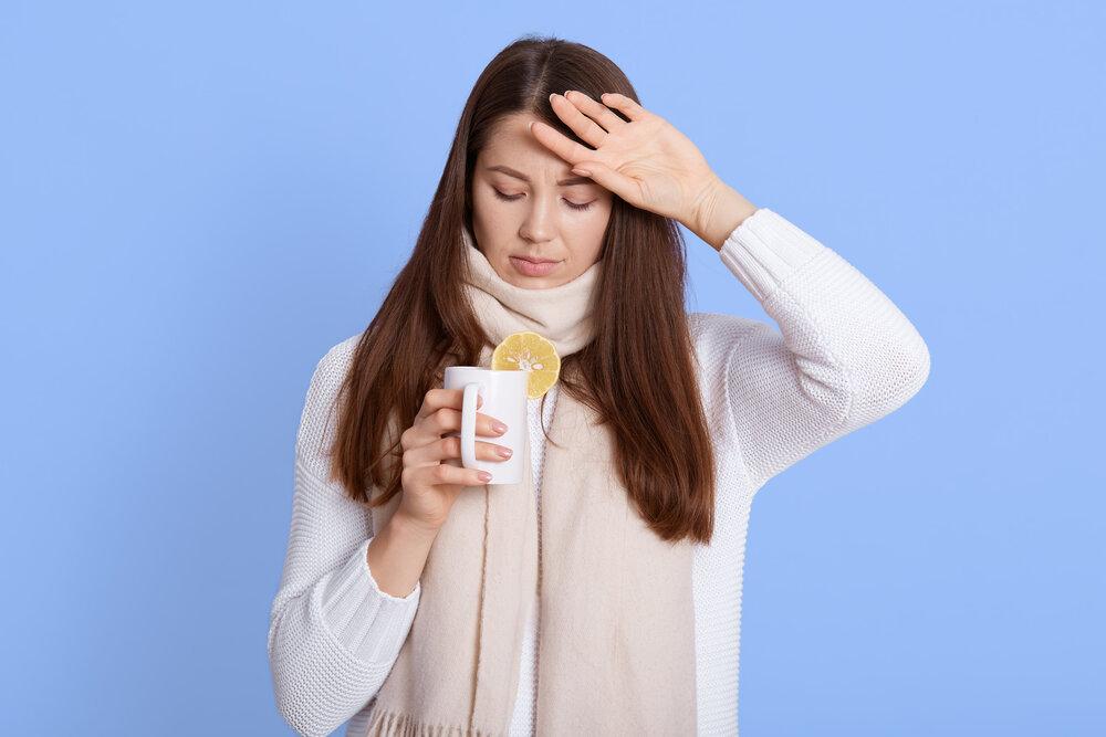 Liečba zápalu pľúc. Portrét chorej mladej ženy zabalenej v šatke, ktorá pije horúci čaj, má zápal pľúc