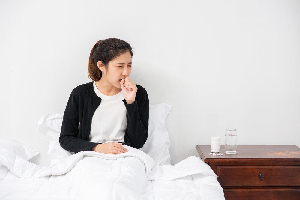 Žena zakašľala, zakryla si ústa rukou a posadila sa na posteľ.