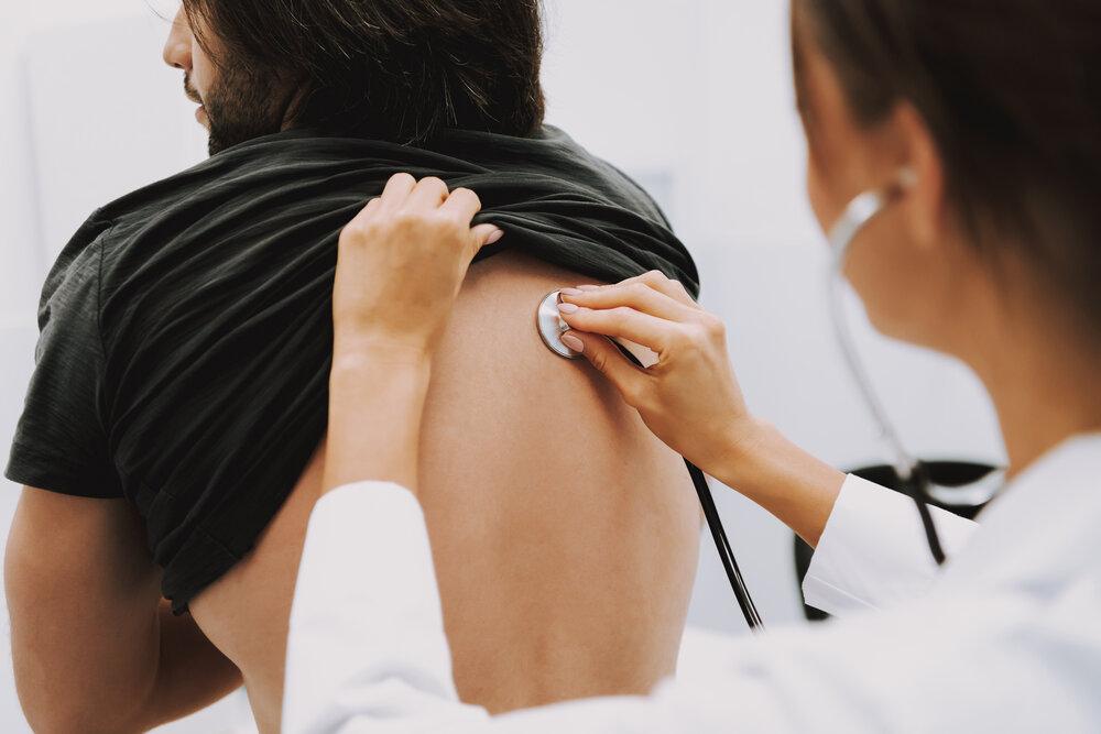 Doktorka počúvajúca hrudník so stetoskopom.