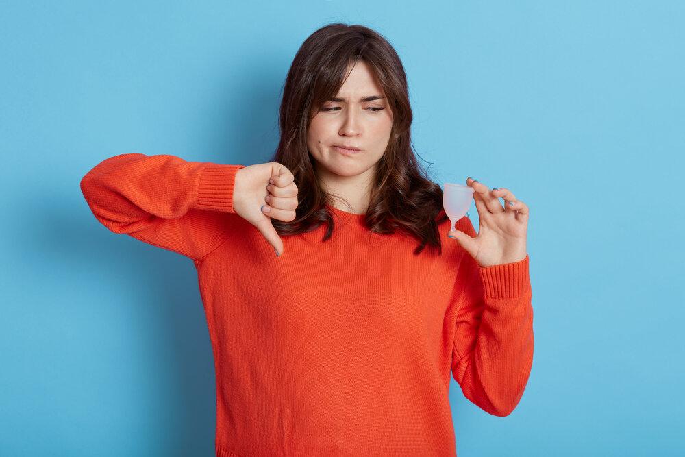 Nespokojná brunetka drží menštruačný pohárik, ktorý jej nevyhovuje. Ukazuje palec dole.