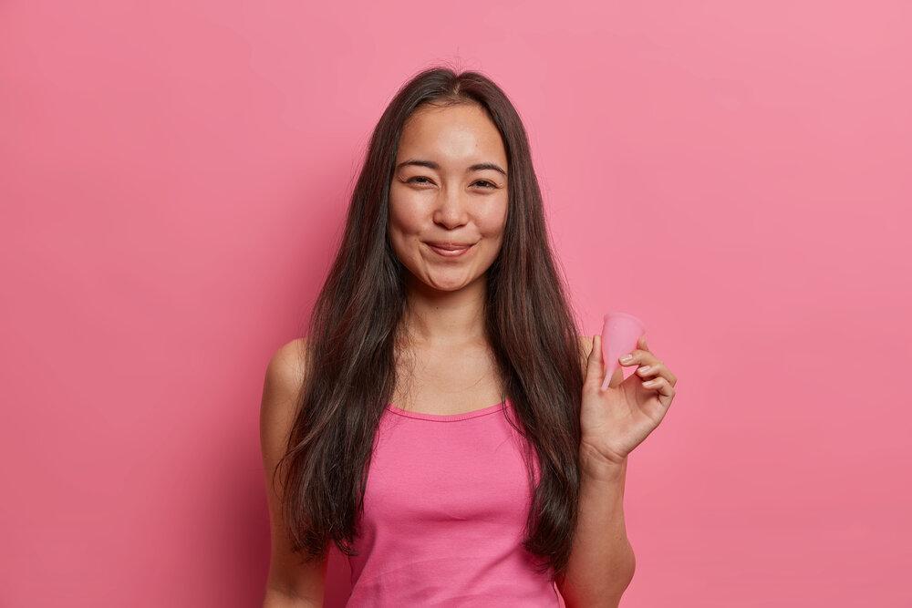 Pozitívna tmavovlasá ázijská žena drží menštruačný kalíšok zo silikónovej alebo latexovej gumy ako ekologickú alternatívu k vložkám a tampónom
