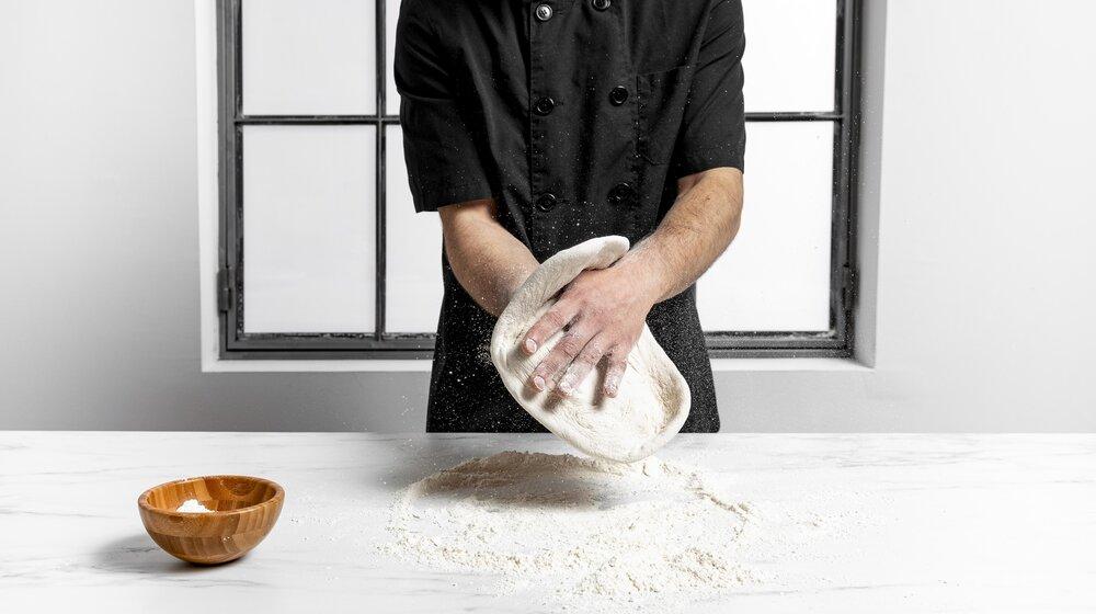 kluchár pripravuje pizzu podľa tradičného receptu