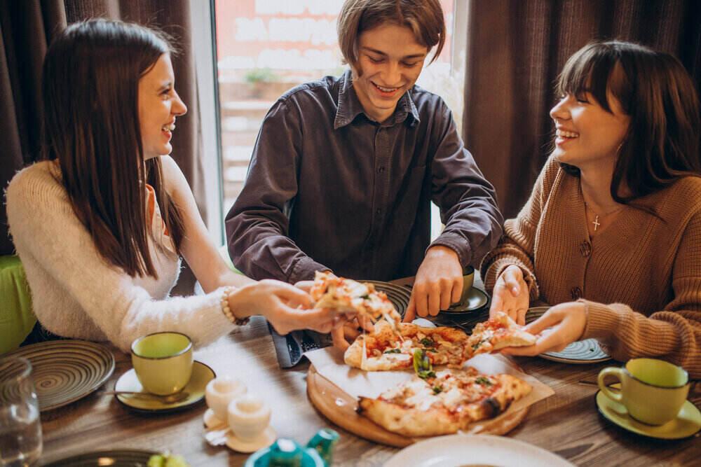 Traja kamaráti spolu jedia pizzu v kaviarni
