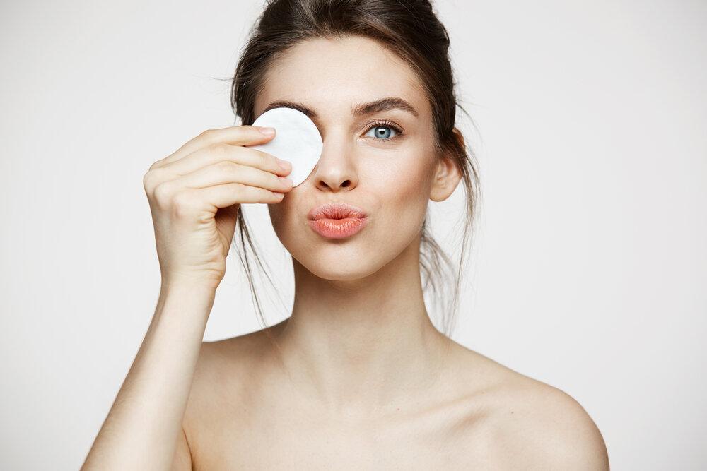 Krásna brunetka s čistou dokonalou pokožkou, ktorá skrýva oko za bavlneným tampónom na odličovanie. Koncept zdravia a krásy.