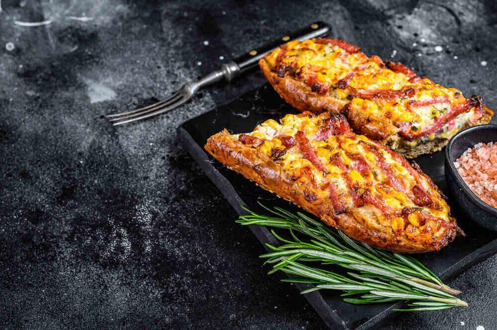 Horúci pečený bagetový sendvič so šunkou, slaninou, zeleninou a syrom.