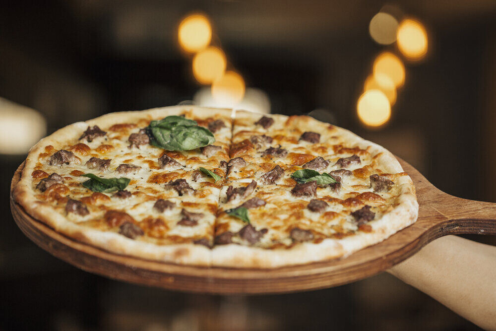 Pizza so zmiešanými ingradienciami na drevenej doske