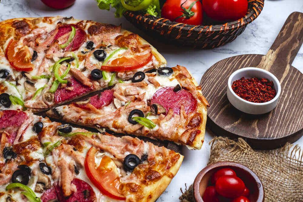 bočný pohľad na pizzu so salámou, zelenými paprikami, paradajkami, čiernymi olivami a syrom na stole