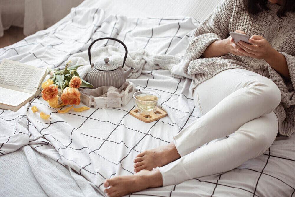 Žena odpočíva v posteli s čajom, knihou a kyticou tulipánov.