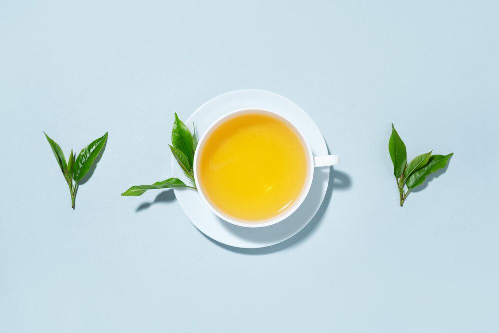 Zelený čaj varený v šálke s čajovými lístkami na modrom pastelovom pozadí.