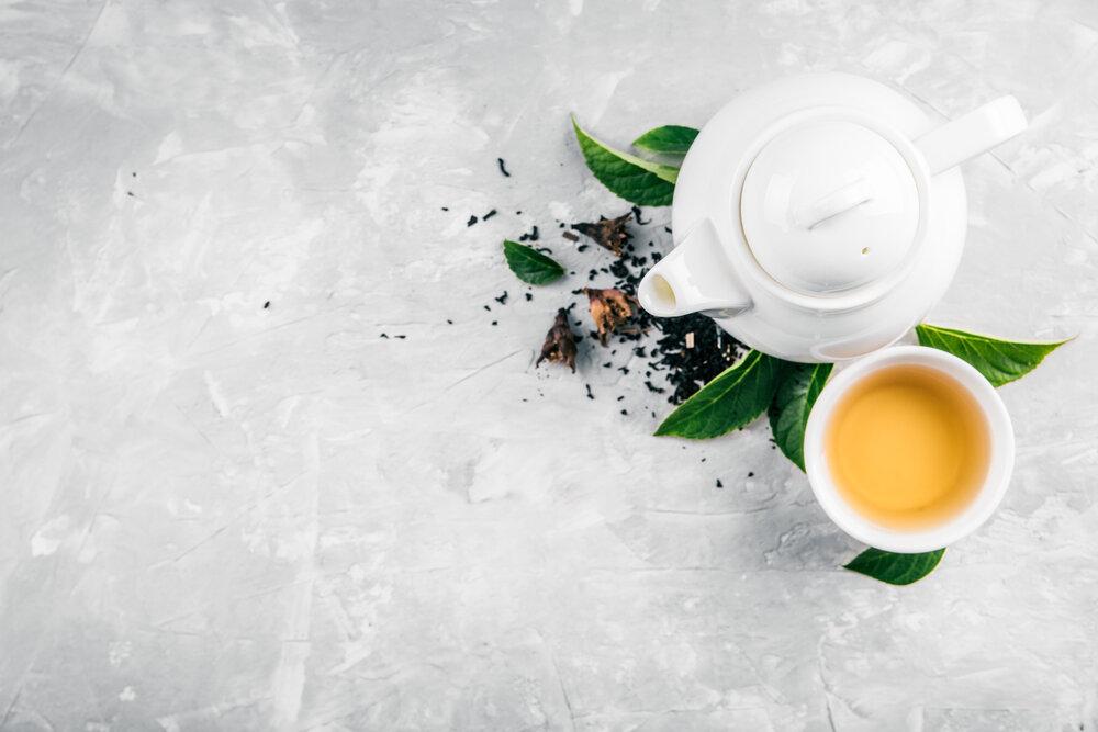 Zelený čaj, šálka a kanvica na čaj s lístkami na sivom betónovom pozadí.