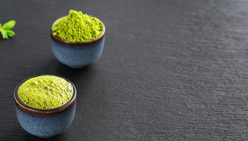 Zelený čaj Matcha v modrej keramickej miske, vedľa misky je prášok zo zeleného čaju Matcha.