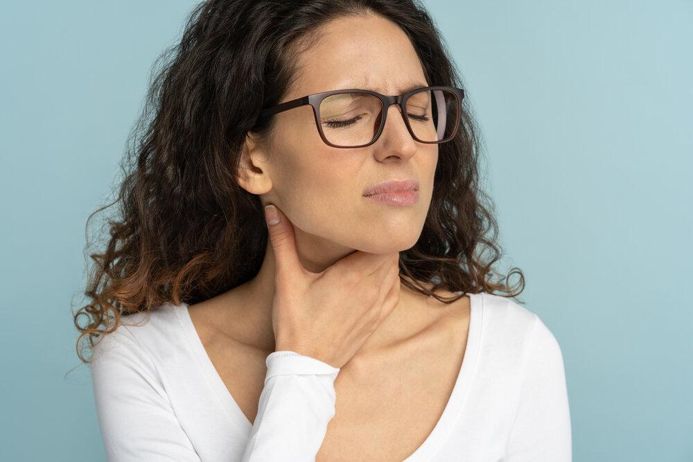 Žena s bolesťami v krku, bolestivým prehĺtaním a pálením záhy