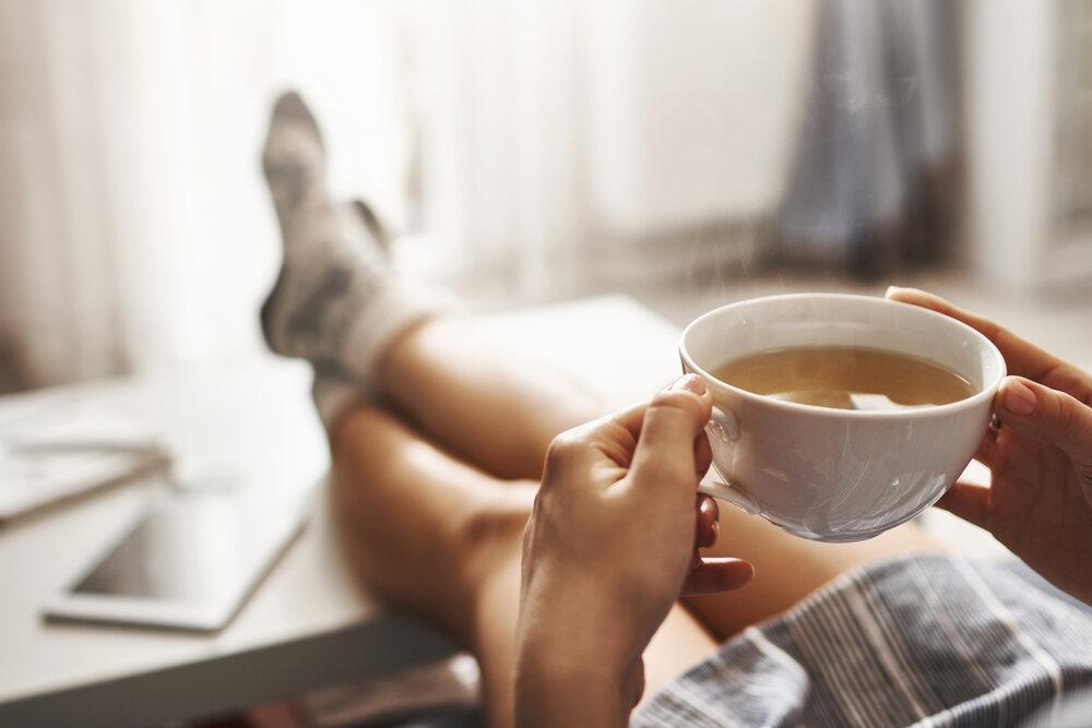 Šálka čaju na chlad. Žena leží na gauči, vyložené nohy na konferenčnom stolíku, pije horúci čaj a užíva si ráno, je zasnená a uvoľnená.