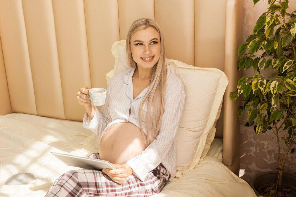 šťastná tehotná žena so šálkou čaju a tabletom v posteli doma