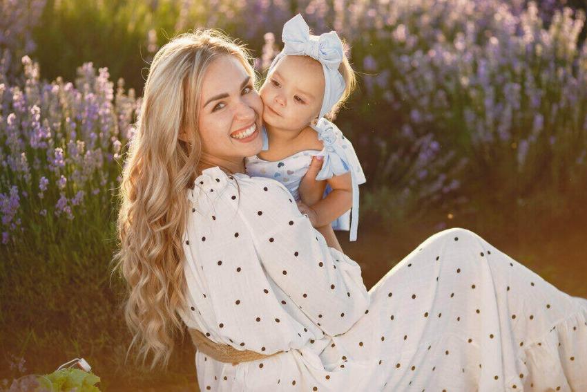 krásna mama v bodkovaných šatoch a jej mladá dcéra pózujú pri levandule