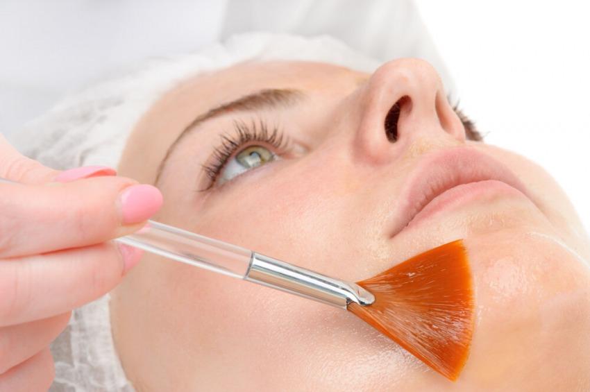detailný záber na ženu na kozmetike, ktorej robia chemický peeling