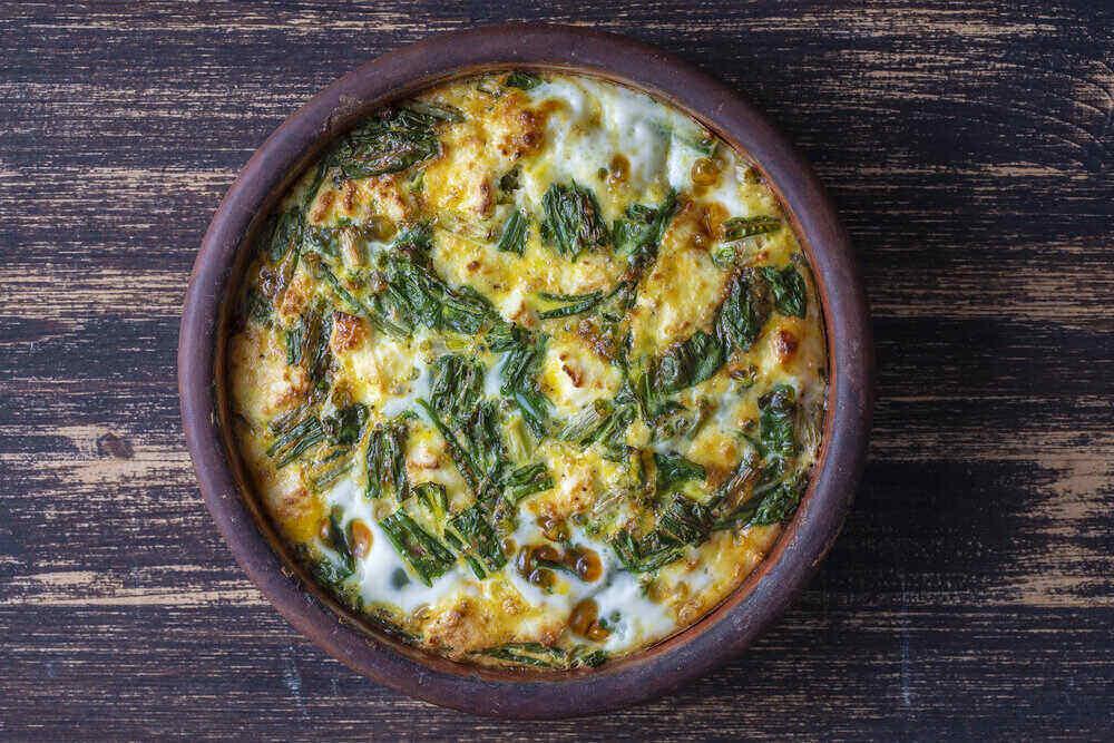 Jednoduché vegetariánske jedlo. Vajíčko, korenie, cibuľa, syr a listy zeleného medvedieho cesnaku na stole, zblízka. Zdravá vaječná omeleta.